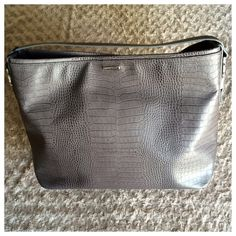 """Thomas WyldeAuthentic Gray Embossed Cowskin Tote Unbelievable, pristine condition, BNWT, $1825 Authentic Thomas Wylde XL Gray, embossed Tote. Appx 19""""W, 14"""" H, 7"""" Deep. Short 6.5"""" drop. Made with the finest quality Cowskin leather with natural skin variations.  Inside: two open pouches and one zipper side pouch.  Plastic protective cover is still on interior nameplate as well as one outer plate.  Signature silver skulls are on each side of the handle.  Ultimate carryall bag, perfect for…"""