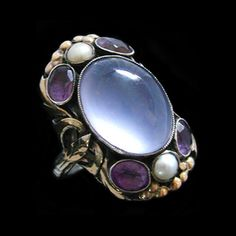 Bernard Instone. Arts and Crafts ring. Silver, gold, moonstone, amethyst and pearl. Silver and gold ring set with a central moonstone, amethysts  and pearls in a border of gold leaves and bobbles. English, c. 1920. Mark for Bernard Instone. Sold by Van Den Bosch.
