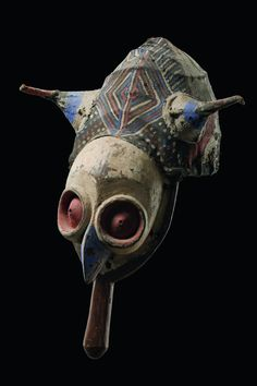 D. R. Congo, Yaka wood, fabric, white, black, red and indigoblue pigment, plug-shaped wooden handle, carved with a bird face (owl?), rattan bonnet coated with plant fibre and fabric, forming a superstrucure with two antenna-like projections, min. dam., small missing parts (fabric), slight traces of abrasion