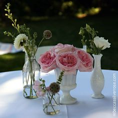 Pink garden roses, scabiosa pods, sweet pea, white lisianthus, delphenium and dahlias displayed in vintage glass bottles and milk glass