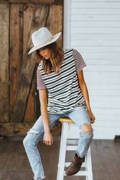light grey hat, multi-colored striped shirt, light wash ripped skinnies and brown boots.