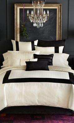 Super sophisticated, luxurious cream and black bedding against a pure black wall with gold framed blackboard. Purple carpet and ribbon with mistletoe hung behind the bed add to the wit of the scheme. And the chandelier - no other type of lighting could have been used.