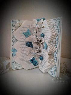 This unique book sculpture tells its story in a beautiful way by a display of crisp patterned folds, book page lace, origami flowers and hand made roses made from matching book pages and blue card stock. So many flowers are nestled in between the pages of this book the butterflies just cant