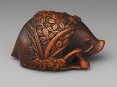19th Century wood Netsuke depicting a boar resting on bush clover
