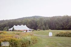 Gorgeous view of the sailcloth tented reception set in a field with wildflowers at Topnotch Resort in Stowe, VT.  LOVE this venue for classy, yet rustic outdoor weddings in New England.  @topnotchresort