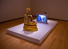 Nam June Paik Golden Buddha, 2005 Video installation with monitor and closed circuit video camera, painted bronze Buddha with the artist's additions in permanent oil marker Nam June Paik, Asia Society, Western Philosophy, Golden Buddha, Fluxus, Video Installation, Museum Exhibition, Painting Videos, Germany Travel