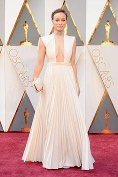 Olivia Wilde com decotaço e plissado branco Valentino mais joias Neil Lane e bolsa Roger Vivier