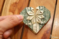 How to Fold a Dollar Into a Heart. Make money a little more fun by folding a dollar bill into a basic heart shape. You can also take it a step further if you're more advanced at origami by adding a pocket that holds a quarter, too. Dollar Bill Origami, Money Origami, Origami Paper, Dollar Bills, Money Lei, Origami Boxes, Origami Ball, Origami Ideas, Fun Origami