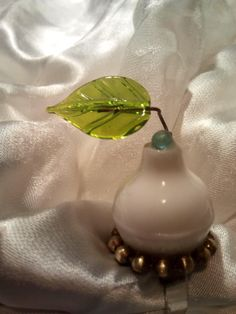 """Anello regolabile """"The leaf"""" realizzato con  elemento in resina colore bianco  circondato da piccole sfere in metallo e sormontato da boule in vetro di Murano turchese  e da foglia, sempre in vetro di Murano, realizzata a lume. Pezzo unico e non ripetibile"""