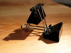 Binder clips to an iPhone stand.  You just put one arm of the first clip through both arms of the second, and twist it so it locks. Take the other arm off the first clip so it sits flat on the table, and you're done!