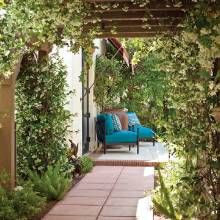 An arbor draped with star jasmine leads to a terrace off the master bedroom. Landscape architect Chad Robert added a colored-concrete walkway under the existing structure and scored it to resemble tile. - PHX Home and Garden
