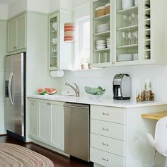 Most cabinet companies offer a wide range of special-use storage units so you can mix and match pieces to get the type of storage you need. Here a vertical row of cubbies stores wine bottles alongside two cabinets of shelves. Clear glass doors on all three wall cabinets expand the sense of space in a small kitchen and show off dinnerware and glassware.