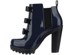A bota com salto tratorado ganha toque feminino com aplicação de três laços em seu cabedal, para criar um calçado que transita por ocasiões diurnas e noturnas.