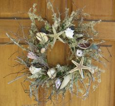 Twig wreath base with starfish & seashells and seaglass. Available at www.thesanddollarstudio.com