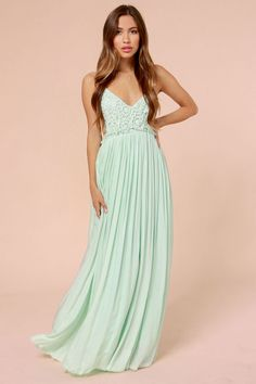 """Picture yourself walking through a flourishing meadow during Spring in the elegant Blooming Prairie Crocheted Mint Maxi Dress! A triangle bodice is packed with elegant Boho appeal thanks to a floral crochet overlay, while spaghetti straps frame an alluring open back. A maxi-length skirt flows gracefully from a gathered and unfinished waistline with hidden elastic, all the way to a dreamy unfinished hem. Lined. Model is 5'10"""" and is wearing a size small. Self: 100% Cotton. Polyester l..."""