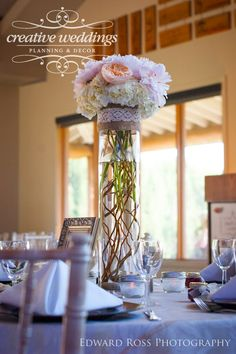 """The """"medium"""" centerpiece was a tall cylindrical vase lined with curly willow wrapped on the inside. Burlap and lace were tied around the top of the container with a posy arrangement of blush pink peonies, 'Juliet' garden roses, 'Vendela' roses and pink astilbe. Design by Janelle of Creative Weddings Floral Designs. Photo courtesy of Edward Ross Photography."""