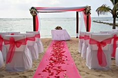 A satin aisle runner with pink flowers...pink flowers on alter but turquoise fabric on altar and chair sashes