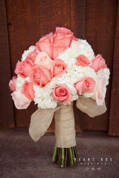 Beautiful bride's bouquet with coral and white roses tied together with burlap ribbon.