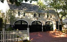 Love the dark arched doors, brick drive, picket fence and side door to apt.