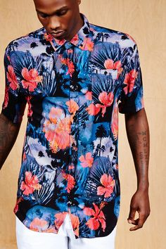 A woven shirt by Super Massive™ featuring a relaxed fit, an allover tropical print, a buttoned basic collar, short sleeves, a buttoned chest patch pocket, and a high-low hem.