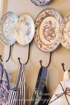 Interiors-decorative plates with hooks. I would attach hooks to wall and secure plates over hooks for a stronger hold.