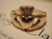 """""""The Claddagh ring (Irish: fáinne Chladaigh) is a traditional Irish ring given as a token of love or worn as a wedding ring."""" """"The Claddagh's distinctive design features two hands clasping a heart, and usually surmounted by a crown. The elements of this symbol are often said to correspond to the qualities of love (the heart), friendship (the hands), and loyalty (the crown).  Claddagh rings may be used as friendship or relationship rings depending on the intention of wearer and, in the ca..."""