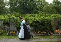 A woman leads a boy through the nearby cemetery during the annual Fronleichnam mass at St. Michaels Church in Seehausen am Staffelsee, Germany, on May 30, 2013.