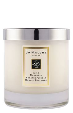 Wild Bluebell Jo Malone Candle | Vibrant sapphire blooms in a shaded woodland. The delicate sweetness of dewy bluebells suffused with lily of the valley and eglantine, and a luscious twist of persimmon. Mesmerising. To uplift, to wind down, or simply to add an air of luxury. Transform the atmosphere with luxury and opulence. Candle burn time is 45 hours and includes lid.