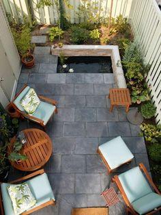 cour intérieure aménagée avec un carrelage de sol gris, un salon de jardin en bois et un petit étang