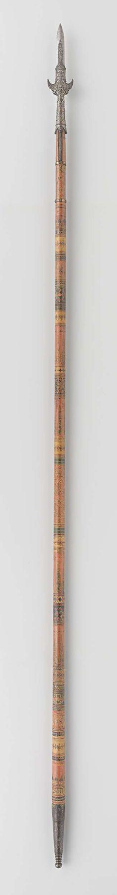   Partizaan van het wapenrek door Indische groten geschonken aan Gouverneur-Generaal J.C. baron Baud, c. 1700 - c. 1800   Ronde houten schacht beschilderd in zwart, rood, geel en groen met voorstellingen van Boddhisattva's, menselijke figuren en geometrische motieven. Onderzijde schacht en omhulsel met horizontale inkepingen toelopend in ovale punt. Omhulsel heeft gepunte bovenrand. Smalle kling uitlopend in scherpe punt. De vier lippen zijn zonder versiering en, om en om, verschillend van…