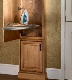 Wall Ironing Board Cabinet stores your ironing board out of sight, but opens easily for use.  By KraftMaid Cabinets, available at Just Cabinets Furniture & More.
