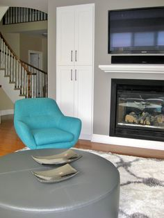 In the foreground, there is a large custom ottoman which not kid-friendly but it acts as a coffee table too. The retro turquoise chair offers extra seating, extra colour and swivels for better TV viewing. Even the staircase in the background was freshened up with white paint and less wood. Open Shelving, Shelves, Turquoise Chair, Round Ottoman, Extra Seating, Glass Table, White Paints, End Tables, Love Seat
