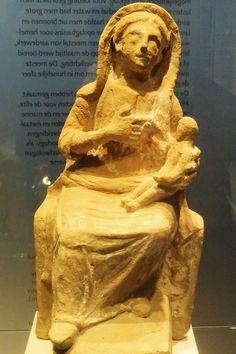 Met haar linkerhand ondersteunt deze godin het naakte kindje op haar schoot. Het zou om de Griekse godin Demeter kunnen gaan, die ook in Carthago bekend was. Zij is de godin van de landbouw. Maar het zou ook kunnen dat het beeld Nutrix voorstelt, de godin van de vruchtbaarheid en de geboorte. Zij werd wijdverspreid vereerd in het noorden van Afrika tijdens de bloeitijd van Carthago. Het aardewerken beeldje dateert ongeveer uit het jaar 100 voor Christus.