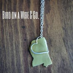Show your love for home with the Mississippi in my Heart necklace. Handmade brass and sterling silver heart. Strung into an 18in. Adjustable cable chain. Lobster claw clasp.