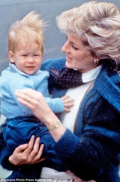 Pictured, Harry cuddles his mother Princess Diana while arriving at a blustery Aberdeen Airport