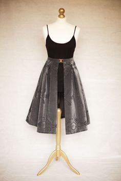 A SKIRTTAIL is a unique, handmade decorative over-skirt that can be worn over the top of any dress or any skirt/top combination that you already have on. It is worn high on the waist and fastened neatly with a gold clasp. The gap in the centre of the fabric elegantly reveals the garment that you have on underneath, instantly updating your outfit. Grey Mid-length available on Etsy.
