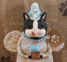"""Hand-sculpted from papier mache, then painted, lightly antiqued for that folk art charm!    This Black & White Cat Birthday Angel comes carrying a cute """"blue""""cupcake! He'sready for the party! Surrounded by angel wings and topped with a pink birthday hat. Accented with a blue vintage style ribbon and paw print hang tag.    Stands 6 1/2inches tall from base to top of hat and is 4inches from wing to wing.    Each piece is signed and dated and is truly one of a kind.    A great gift for you or…"""