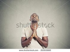 Closeup portrait young man praying hands clasped hoping for best asking for forgiveness or miracle isolated gray wall background. Human emotion facial expression feeling - stock photo