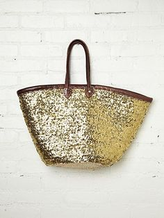 """Gold sequin covered straw tote bag with leather trimming and handles. Top part of inside is lined.  *By Miklos  *Straw, Sequins, Leather  *Import  *14 1/2"""" depth, 24"""" wide across top front, 11"""" wide across bottom front  *8 1/2"""" handle drop"""