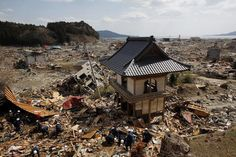 JAPAN-QUAKE/Emergency workers search through debris around a Buddist temple's gate after the magnitude 9.0 earthquake and tsunami near the seaside in Rikuzentakata, Iwate prefecture, March 19, 2011. This picture forms part of a set of 'before' and 'after' images released February 27, 2012 before the first anniversary of the earthquake and tsunami on March 11, 2012. Picture taken March 19, 2011. REUTERS/Aly Song/Files (JAPAN - Tags: DISASTER ENVIRONMENT ANNIVERSARY)