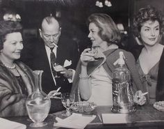 Vivien Leigh and Lauren Bacall at a party, along with Noel Coward and Kay Kendall, circa the late 1950s.