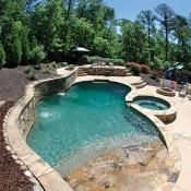 Inground pool freeform concrete pool with an 8' round spa. The landscape is immaculate and beautifully designed