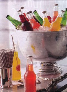 silver punch bowl filled with soda on ice