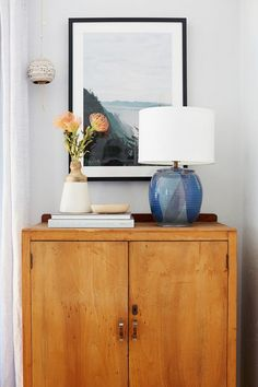 Serene inspired living space with framed art, and vintage dresser styled with a blue lamp and flowers