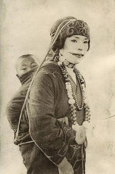 Ainu woman with traditional facial tattoos and a child, taken c.1930. Japan.