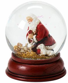 """A glowing Santa Claus with rosy red cheeks kneels beside Baby Jesus in this snow globe that you'll cherish for years to come. 