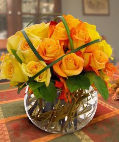 Yellow gold roses criss-crossed with bear grass. Also autumn leaves. Autumn Flower Arrangements