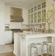 White kitchen, glass cabinet fronts with stainless steel appliances. Nickel stools also. Love the plant/tree