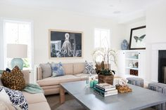 A framed octopus print and ocean blue accents lend a coastal feel to this living room. Contemporary furniture looks sleek and stylish, and white walls and built-ins create an ultra-bright atmosphere.