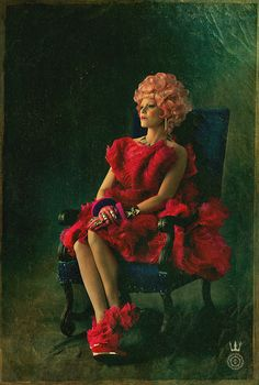 """Capitol Couture - """"Effie Trinket: Head to heel in couture, Effie enchants in an exploding silhouette of chiffon and organza blooms. Never one to waver in her fashionable footwear, her heel-less boots are shod with a golden horse-shoe platform."""""""